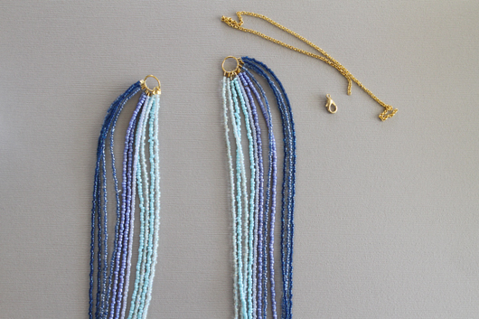 ombre blue seed bead necklace with a gold chain and clasp to the side