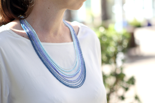 Andrea wearing a white shirt and the completed ombre blue multi-strand seed bead necklace