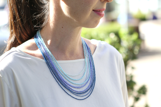 Andrea wearing a white shirt and a blue ombre multi-strand seed bead necklace
