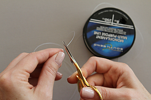 cutting the necklace string with gold scissors