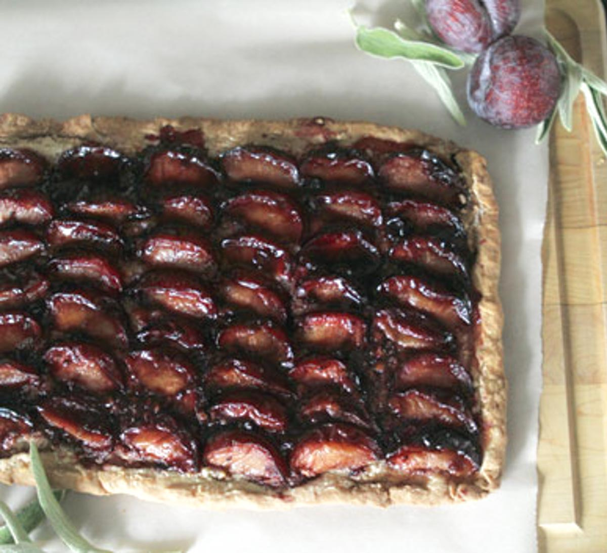 a rustic plum tart on a cutting board sitting on white parchment paper