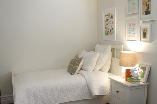 white bed and night stand with colorful photos on the wall
