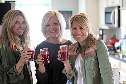 three girls holding beet-juice for a taste-test-
