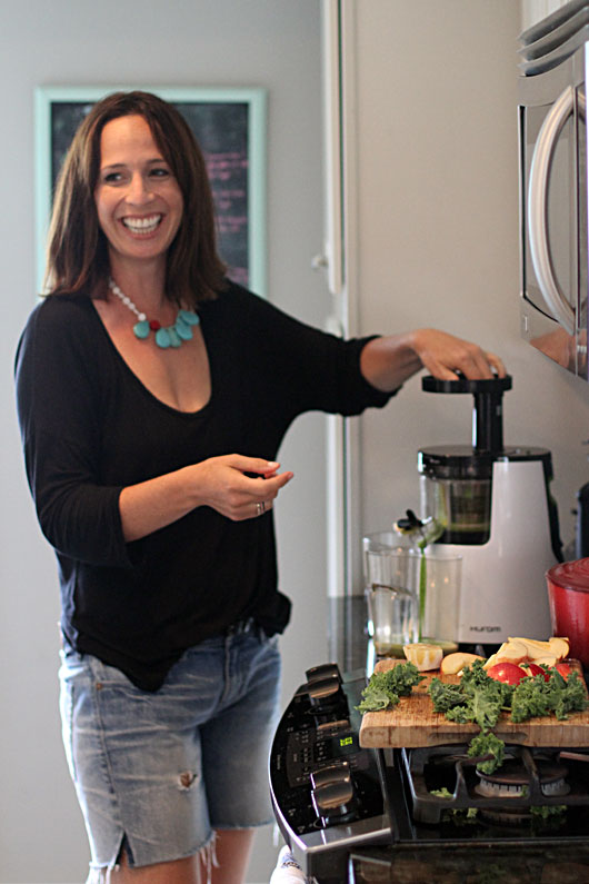 Andrea juicing veggies with her hurom juicer