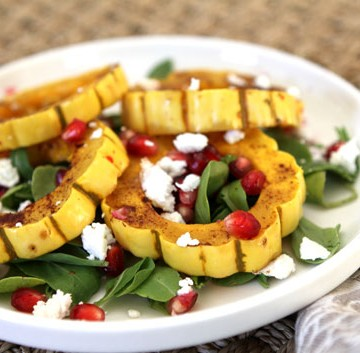 a white plate with roasted delicata squash, greens, pomegranate, and goat cheese