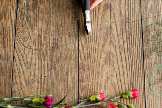 woman cutting green florist wire on wood table