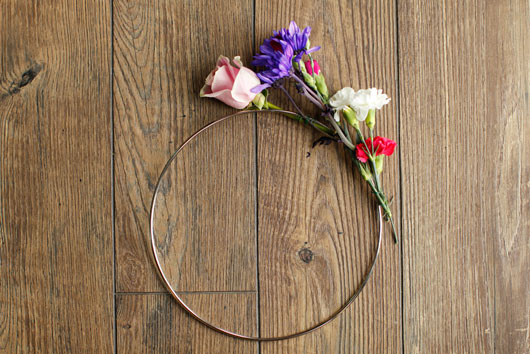 pink roses and purple and white carnations attached to a metal hoop