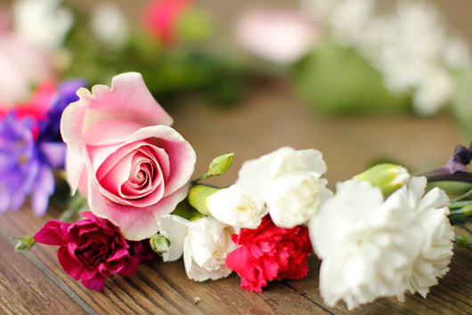 pile of pink roses, and carnations against a wood table
