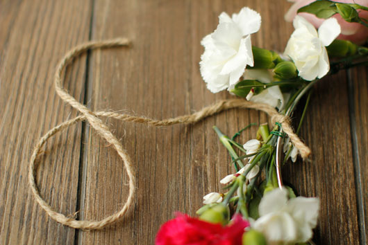 jute string tied to a metal hoop decorated with flowers