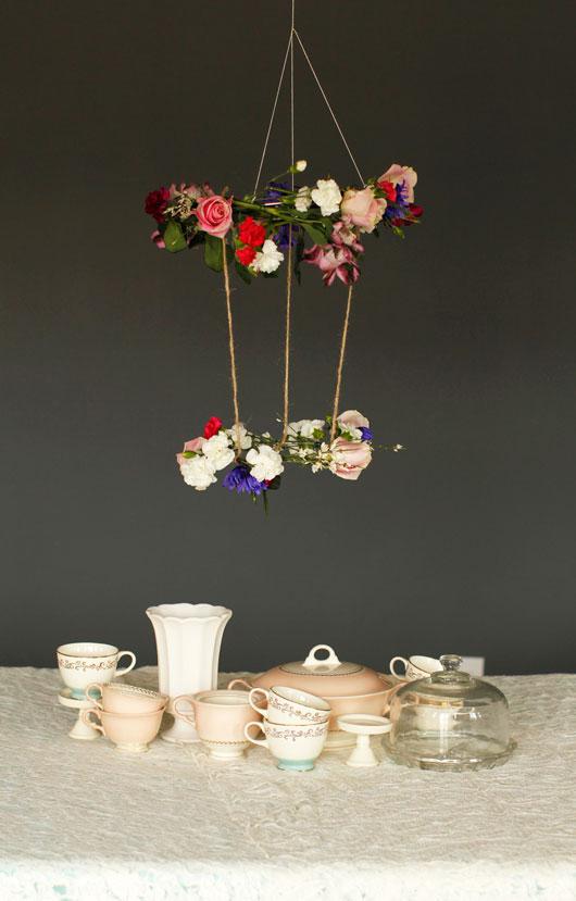 DIY hanging floral chandelier above a table set for tea