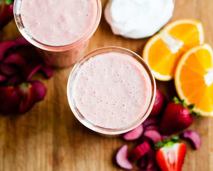 2 glasses filled with strawberry dairy free smoothie, with orange slices