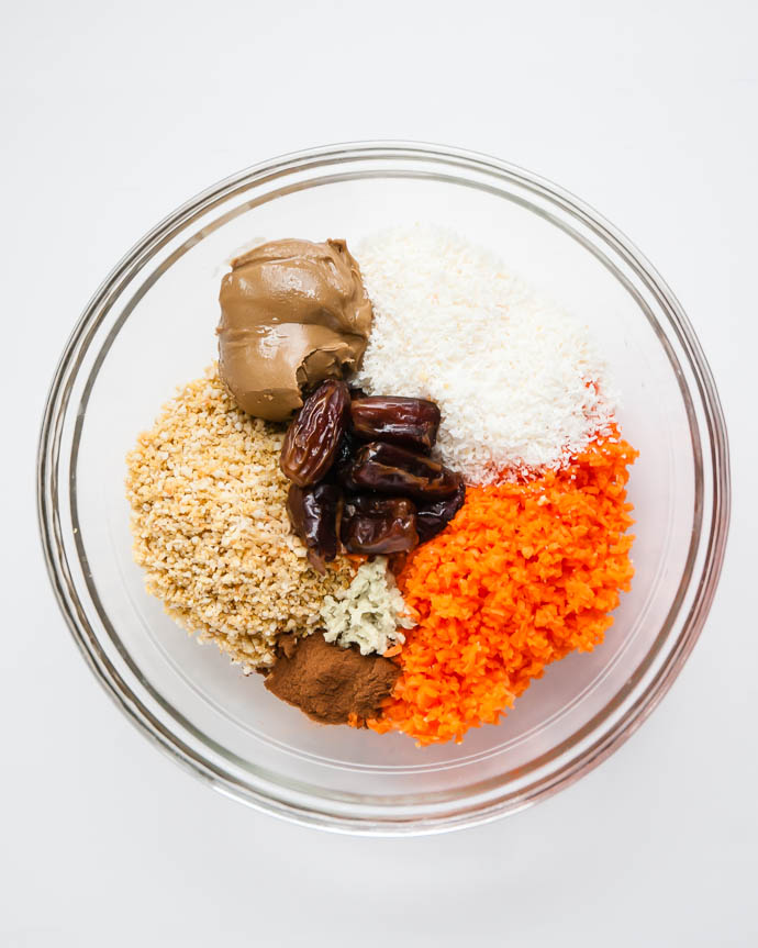 a glass bowl with sunflower butter, dates, cinnamon, vanilla, ginger, coconut, carrots, and cashews