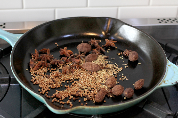 toasting spices in a frying pan- star anise, clove, coriander, cardamom and fennel seeds