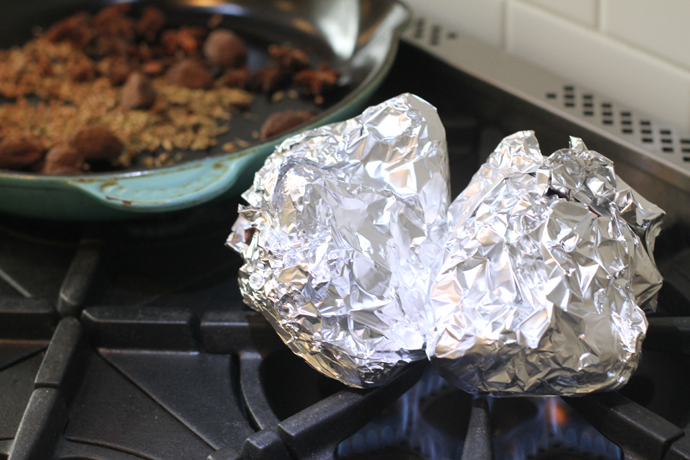 onions being roasted while wrapped in foil on the stove top