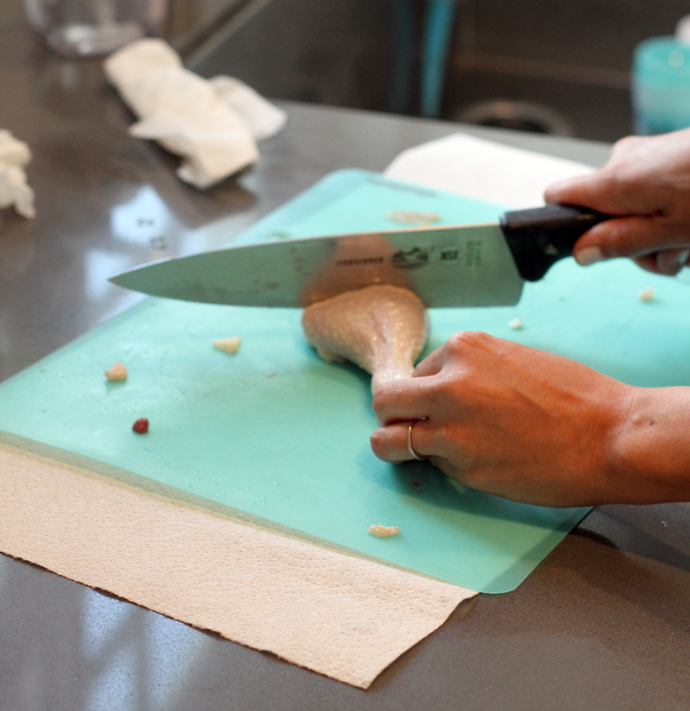 cutting a chicken leg on a turquoise cutting board