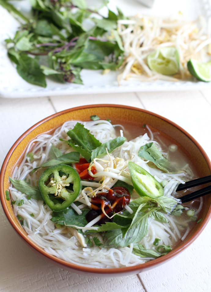 A bowl full of traditional Chicken Pho topped with basil, jalapenos and hoisin