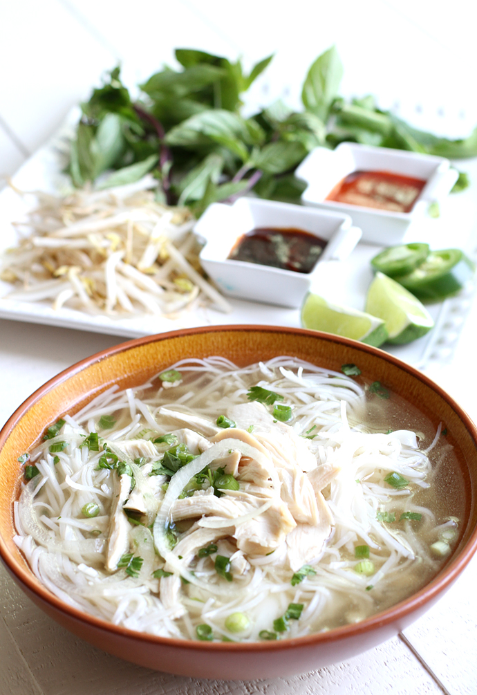 A bowl of Vietnamese Chicken Pho Ga topped with scallions, a white plate of toppings in the background
