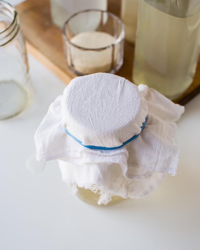 a glass mason jar covered in a white cloth