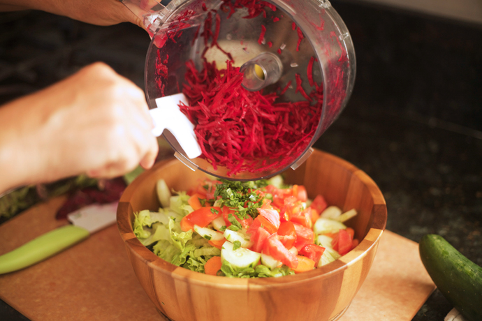 shredded beets from the food processor, being added to a farmer's market salad