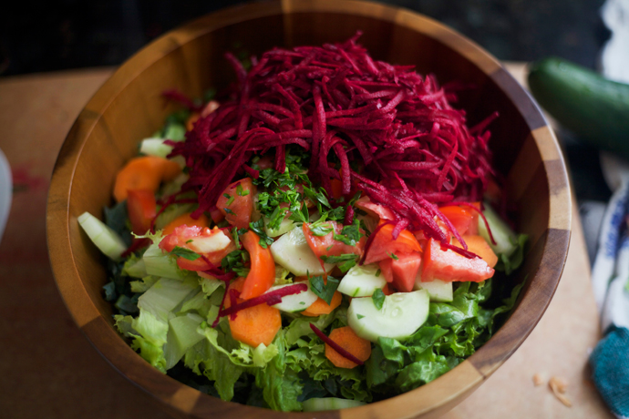 local and in-season salad being assembled in a wooden bowl with beets, carrots, cucumbers