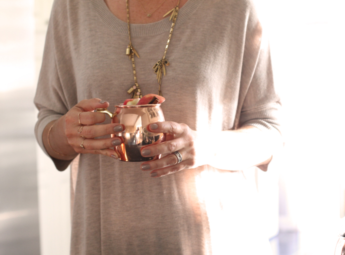 A person in a tan shirt holding an apple cider moscow mule in a copper cup