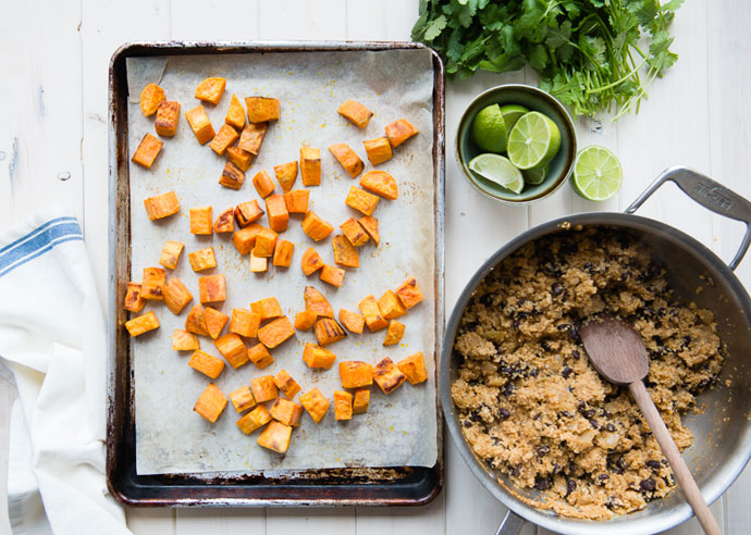 roasted sweet potatoes on a baking sheet, sauce pan of cauliflower rice, and a bowl of limes