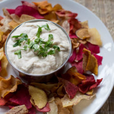 bowl of cashew cream dip surrounded by veggie chips