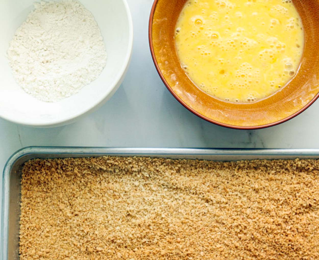 breading station for chicken cutlets, flour, egg, and panko bread crumbs