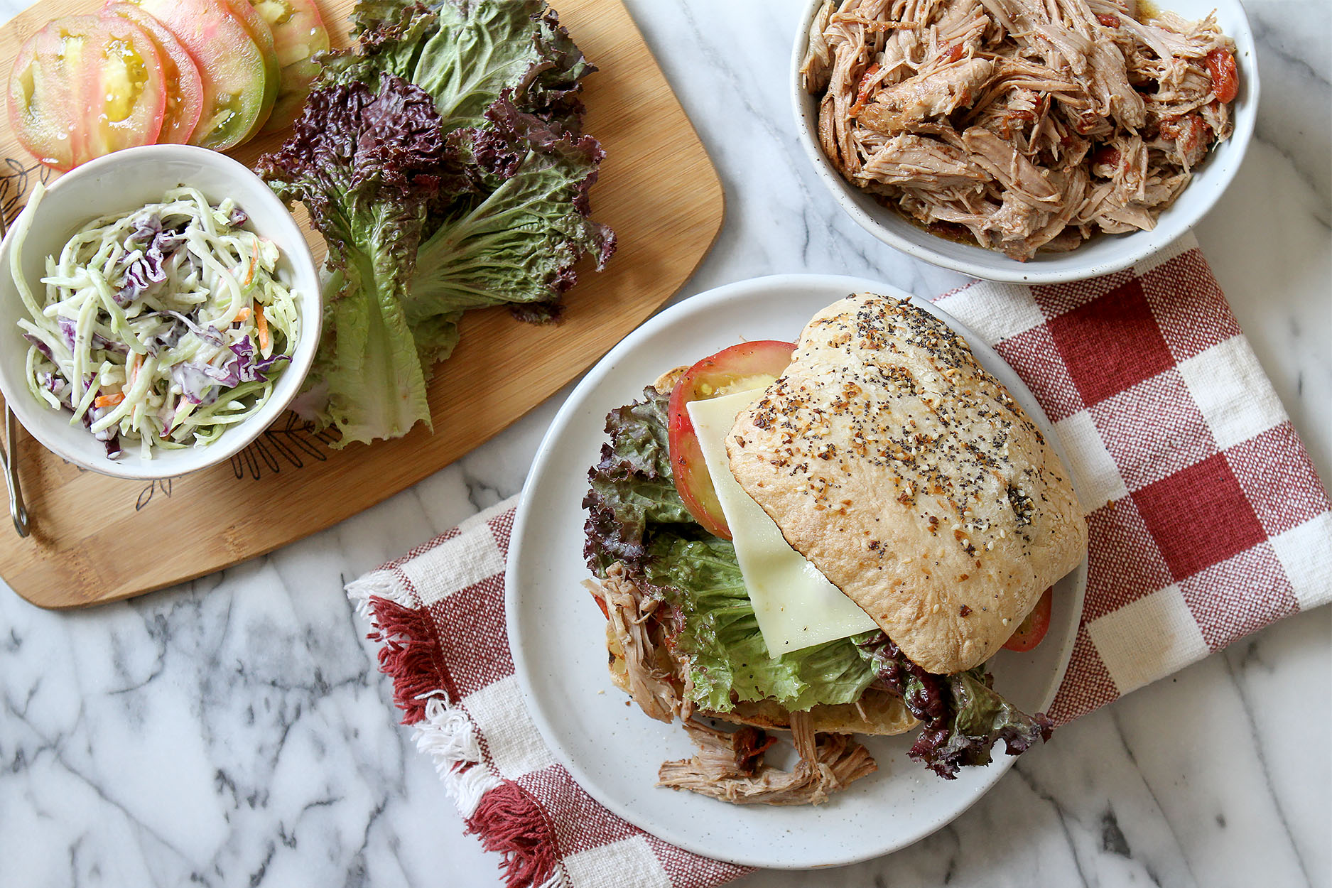 pulled pork sandwich on a white plate sitting on a red and white gingham napkin, a bowl of pulled pork to the side and a cutting board full of lettuce tomatoes and slaw.