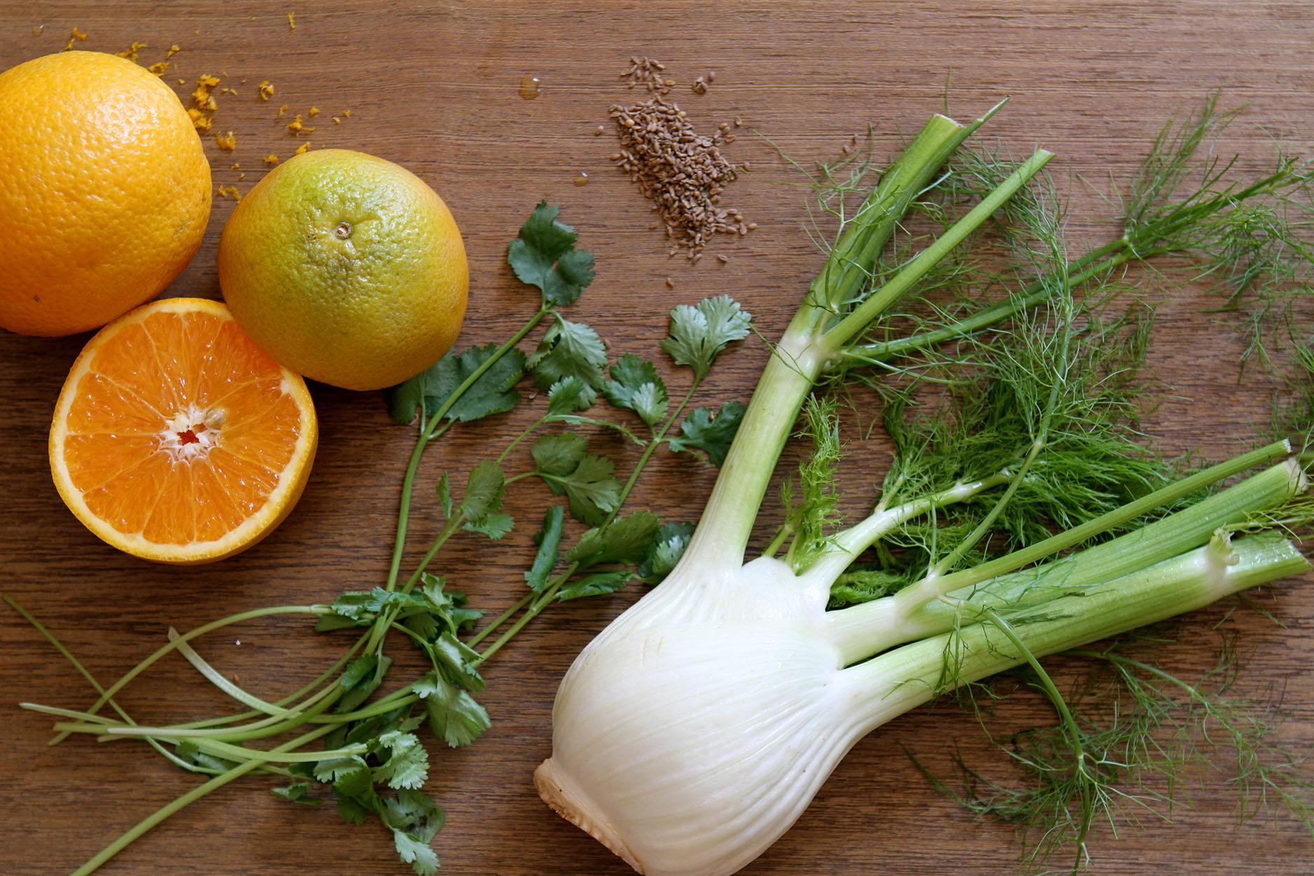 Oranges, parsley, fresh fennel and fennel seeds on a wood cutting board