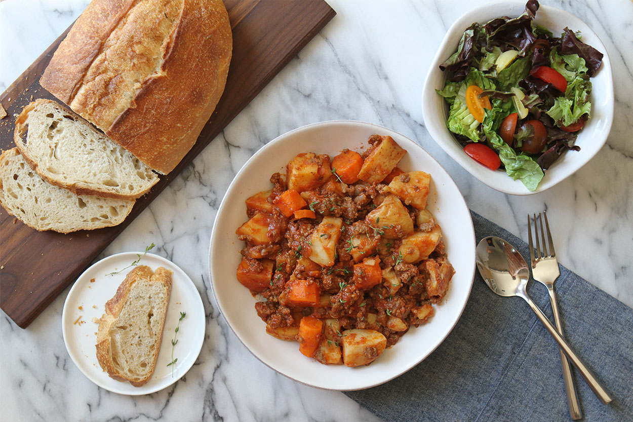 a white bowl of slow cooker beef stew, a loaf of bread on a wooden cutting board and a green salad in a white bowl. A fork and spoon to the side