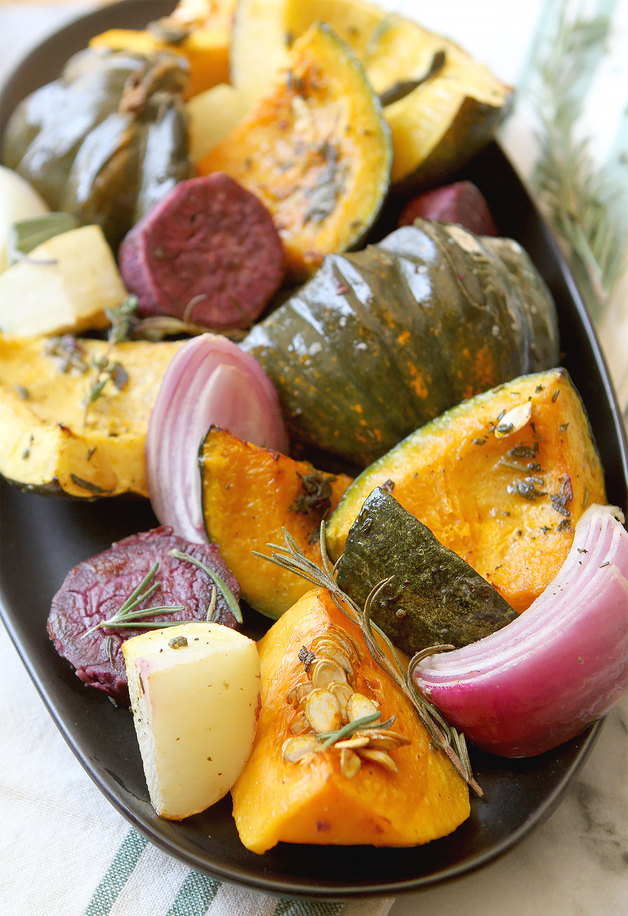 a oblong black plate full of beets, squash, red onions, and sprinkled with rosemary and thyme