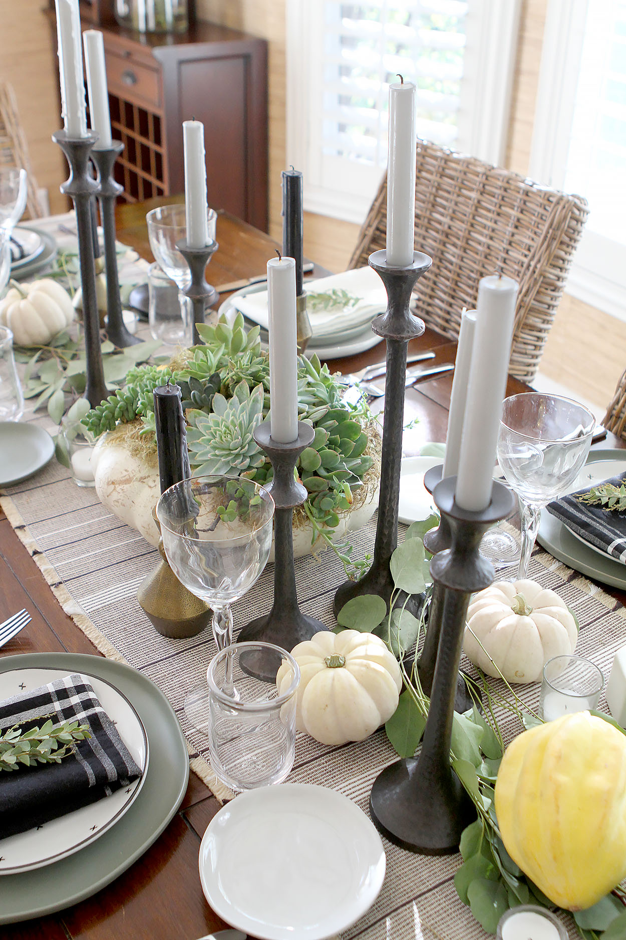 A holiday table set with a table runner, candles, pumpkins, and greenery