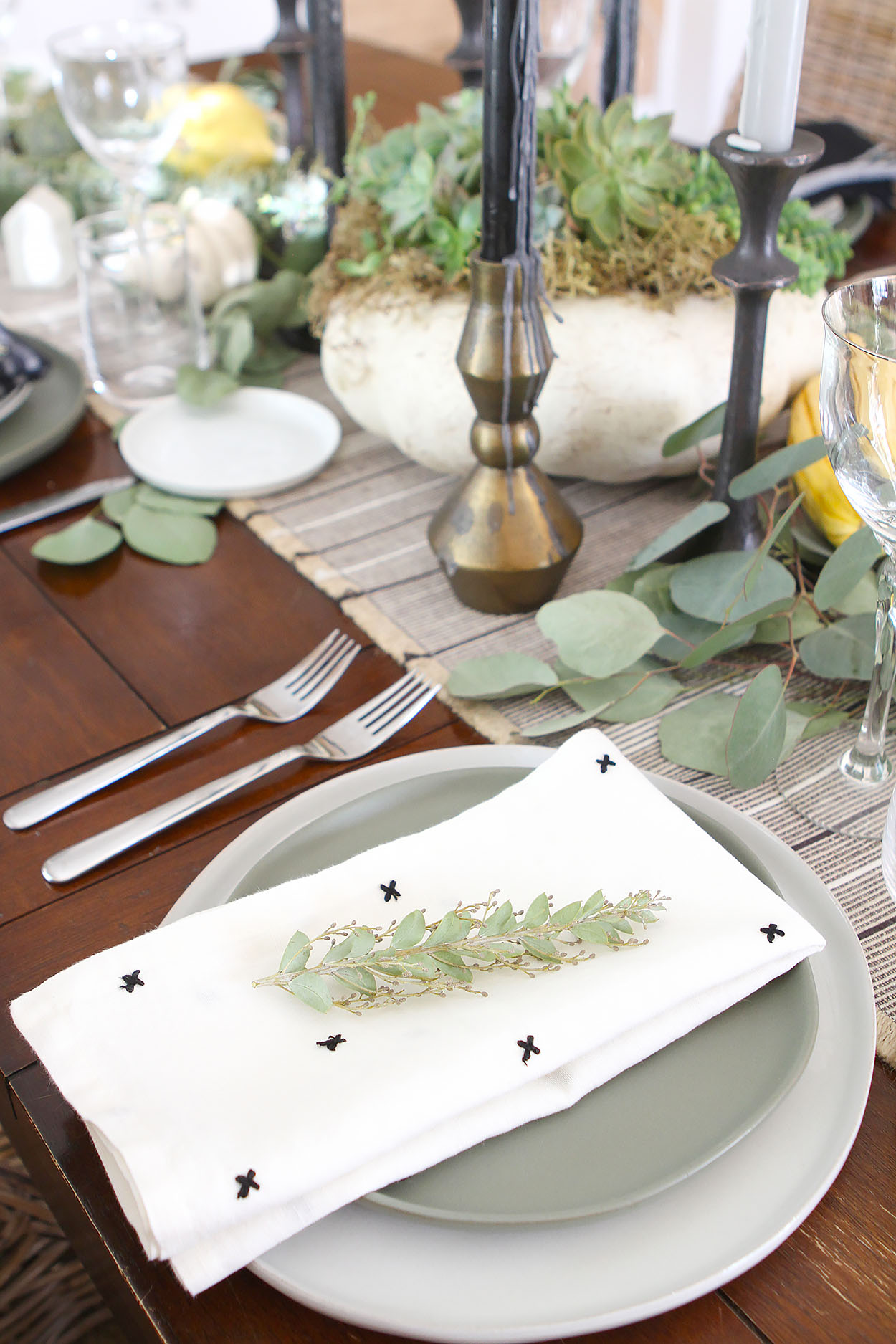 a place setting with two gray plates, a napkin with black cross stitches and two forks