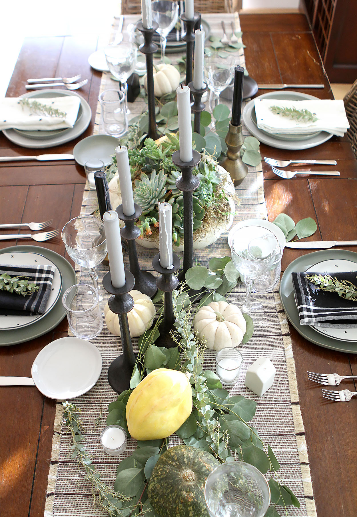 a table centerpiece set with candles, greenery, and pumpkins