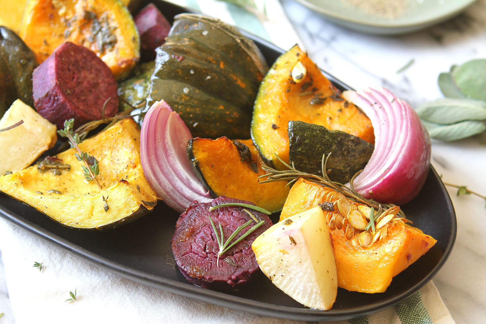 an oblong black plate full of squash, beets, red onions, turnips, and sprinkled with rosemary and thyme