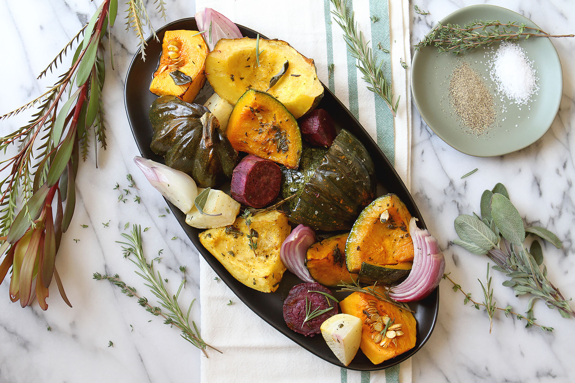 an oblong black plate full of roasted squash, onions, turnips, and beets. Herbs and greenery to the side