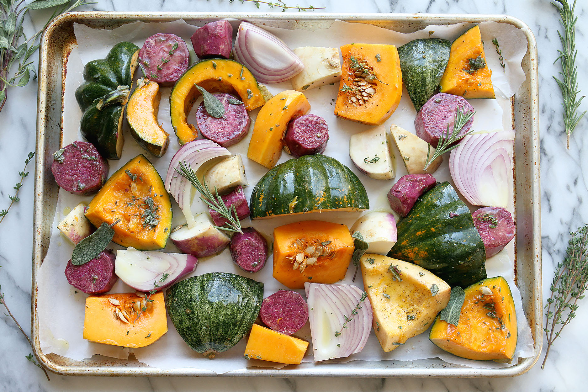 A sheet pan lined with parchment paper, full of squash, red onions beets, and turnips. Thyme, rosemary and sage sprinkled over the veggies