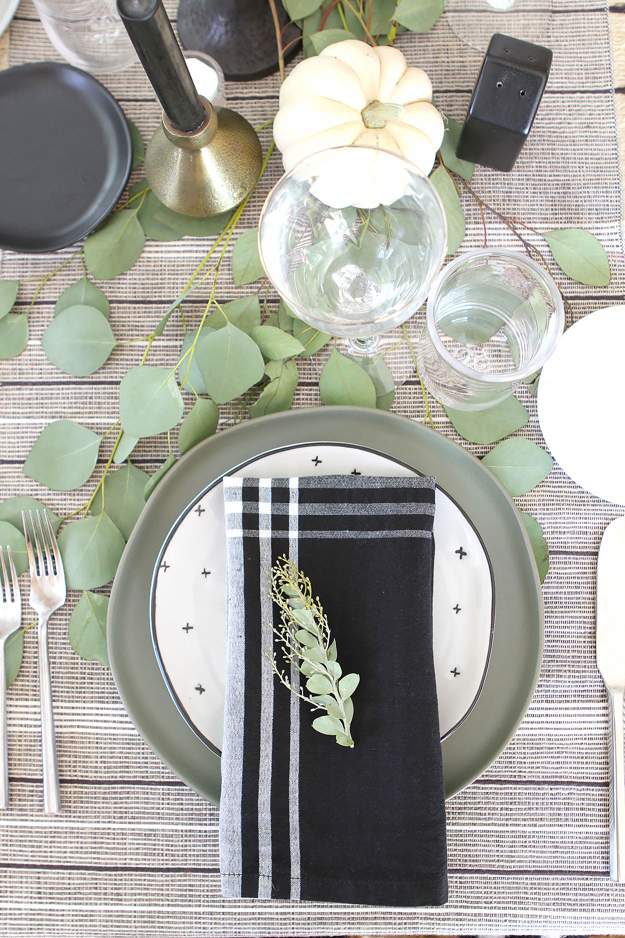 a plate setting with a gray plate topped with a white plate with black x's and a black and white napkin topped with greenery
