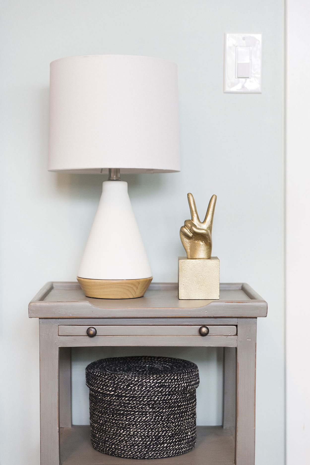 Night stand with a white lamp, gold peace hand and black basket