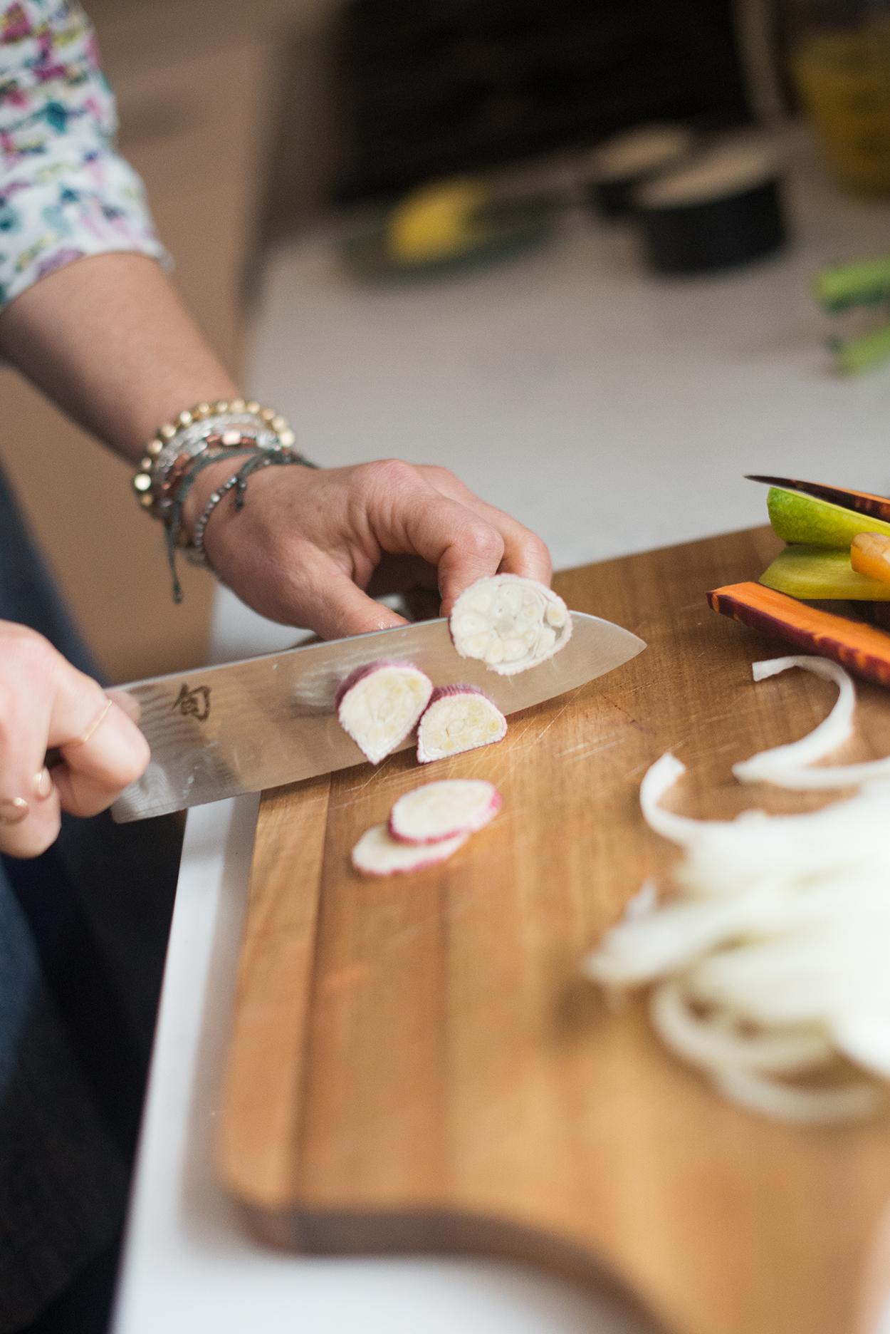 cutting green garlic on a wooden cutting board
