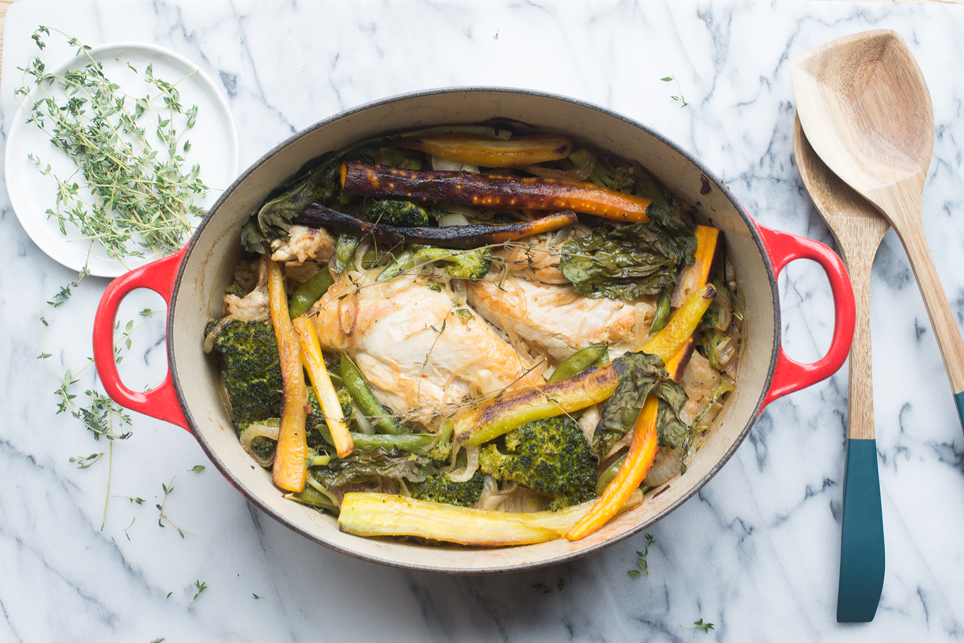 chicken and vegetables in a red dutch oven, with wooden spoons and a plate of thyme to the side