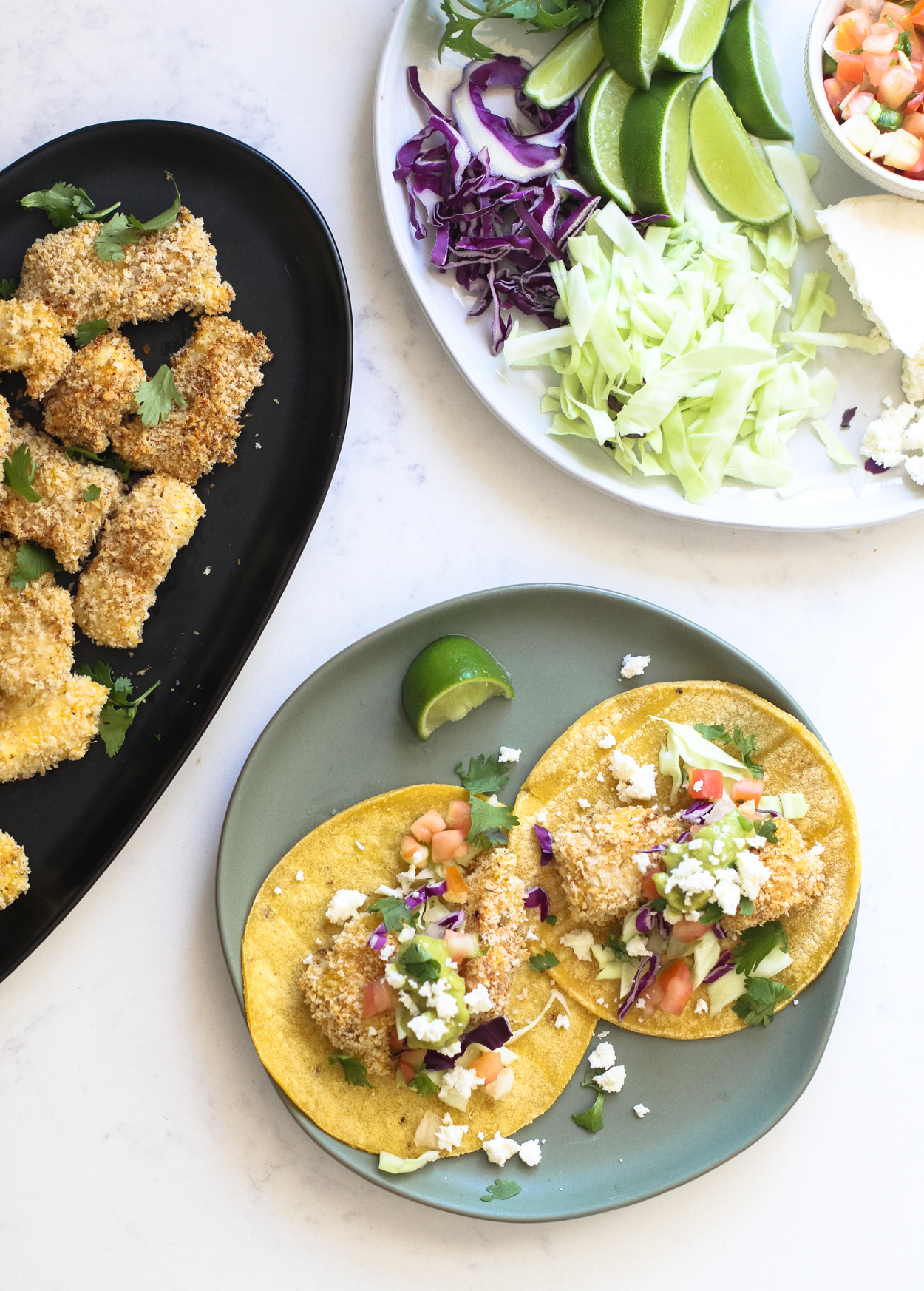 two crispy baked fish tacos on a round blue plate with a lime wedge to the side. A black plate with crispy cod pieces and a white plate with taco toppings in the background