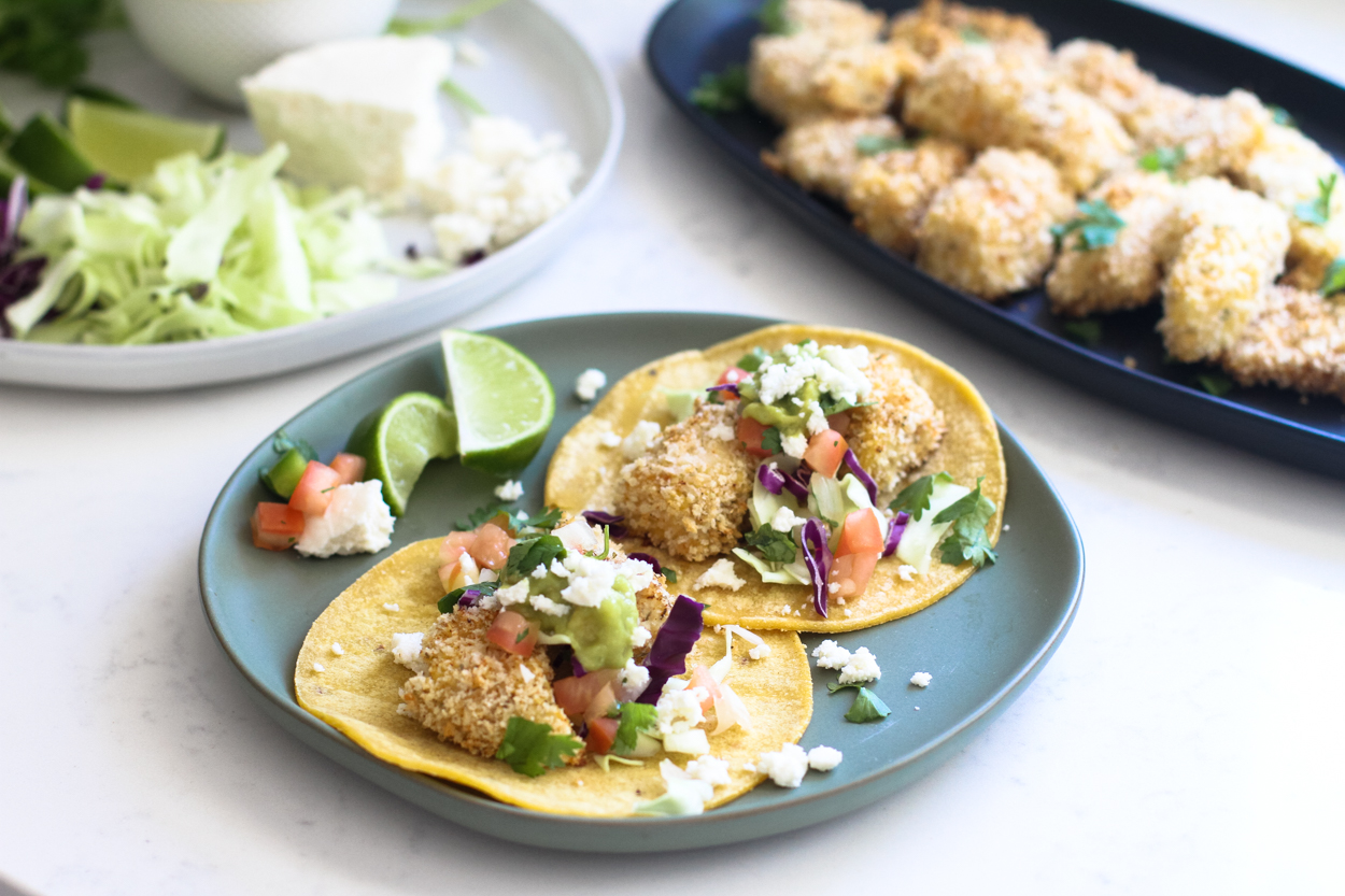 crispy baked fish tacos in tortillas on a blue plate with lime, tomatoes and queso fresco. A black plate with pieces of baked cod and a plate with lettuce and queso fresco in the background.