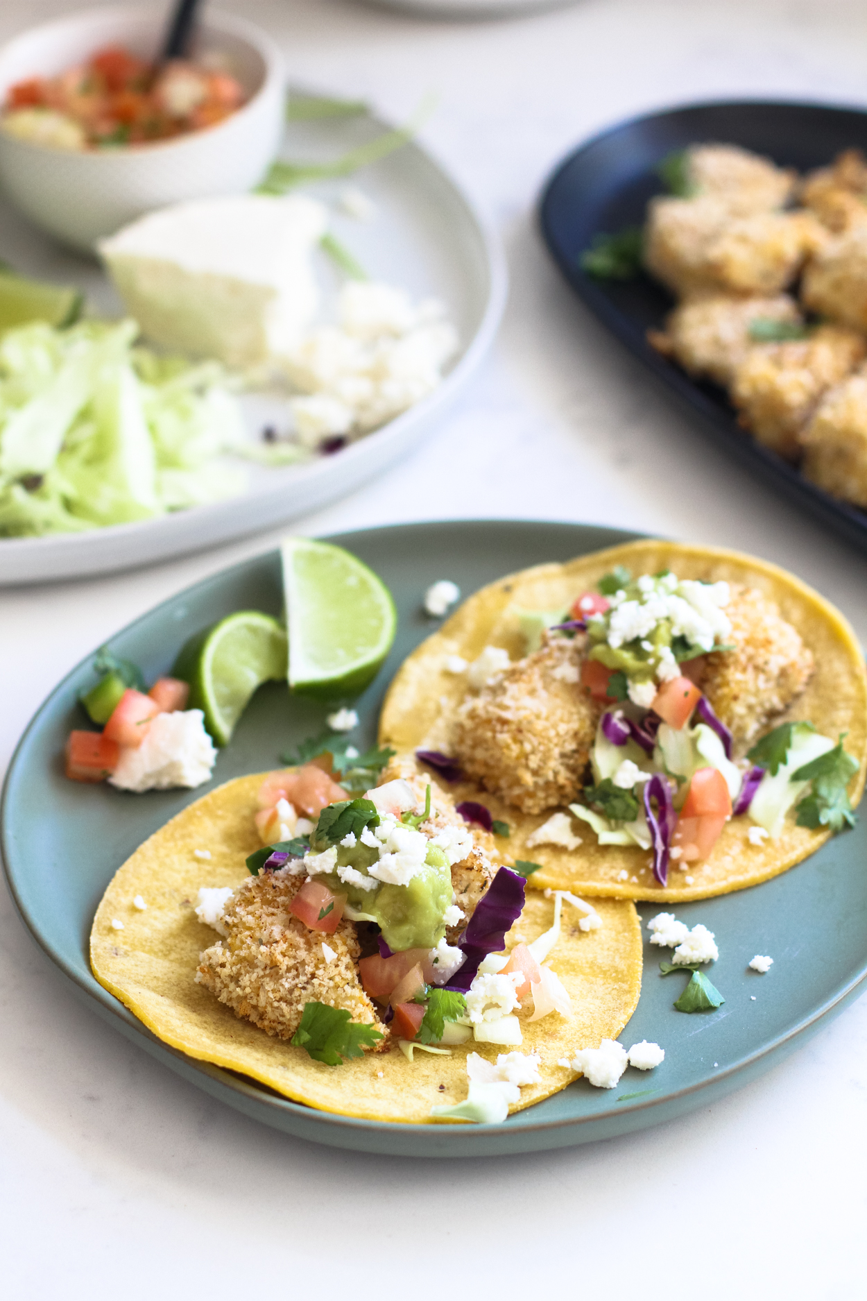 A blue plate with two baked fish tacos, tomatoes, queso fresco and limes to the side. Two plates of taco toppings and baked cod in the background