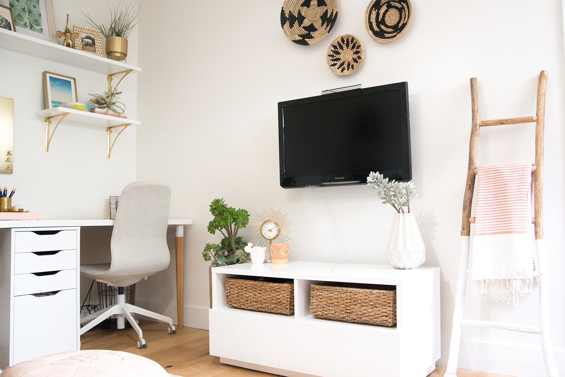 Office space with a white desk and grey chair with white and gold shelves above. A white TV console with baskets and a tv mounted on the wall above