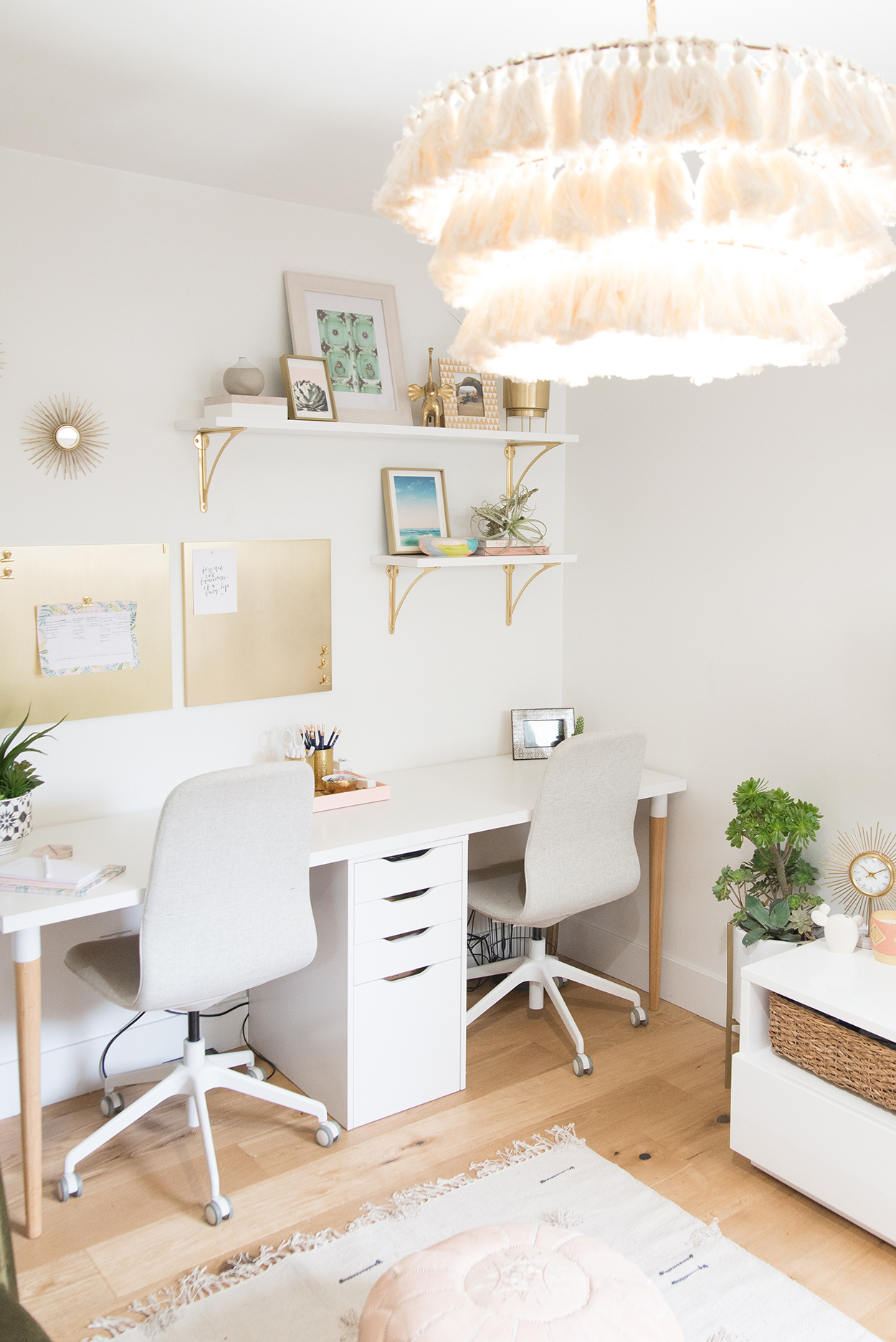 office space with a white desk and two gray chairs, a chandelier with pink tassels