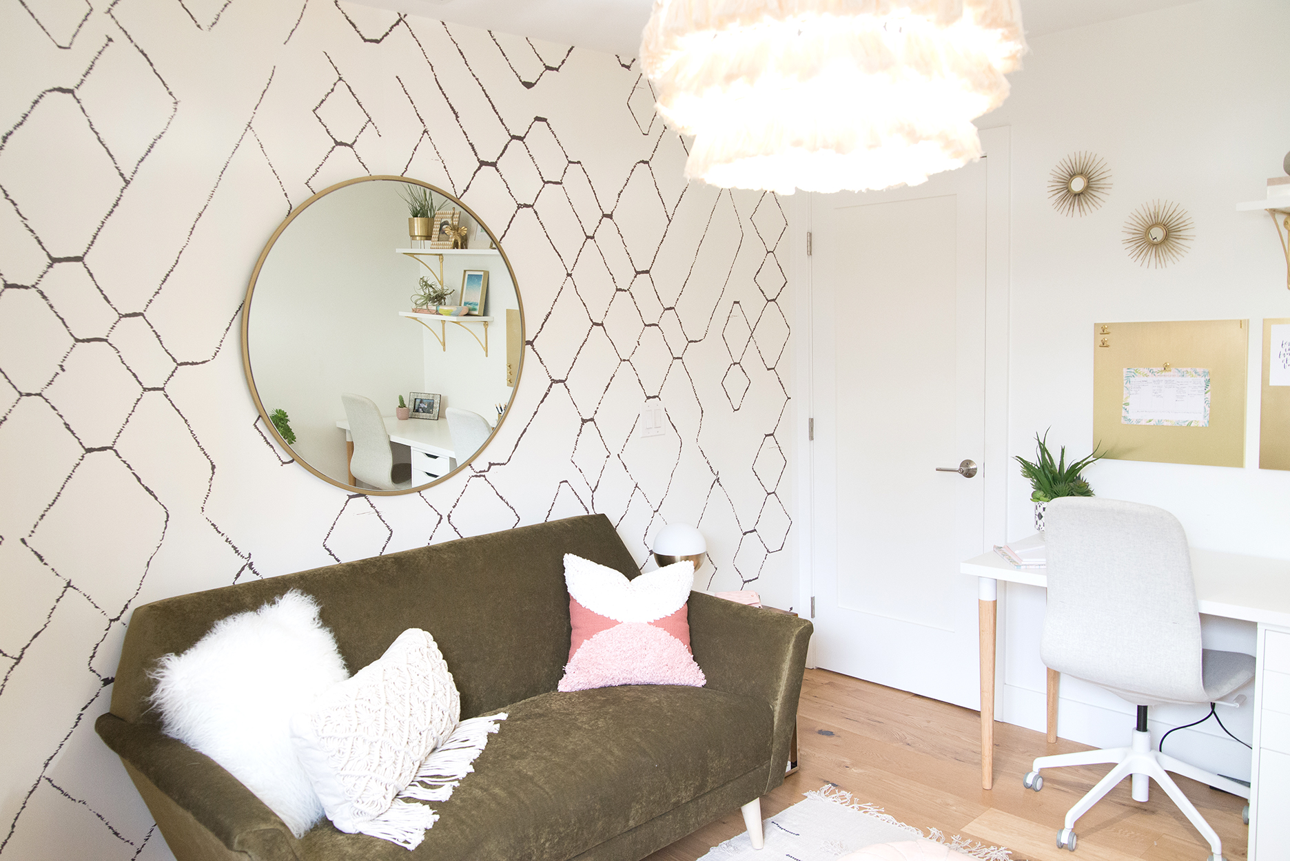 a geometric wallpapered wall with a round mirror, a small couch and a pink tassel chandelier