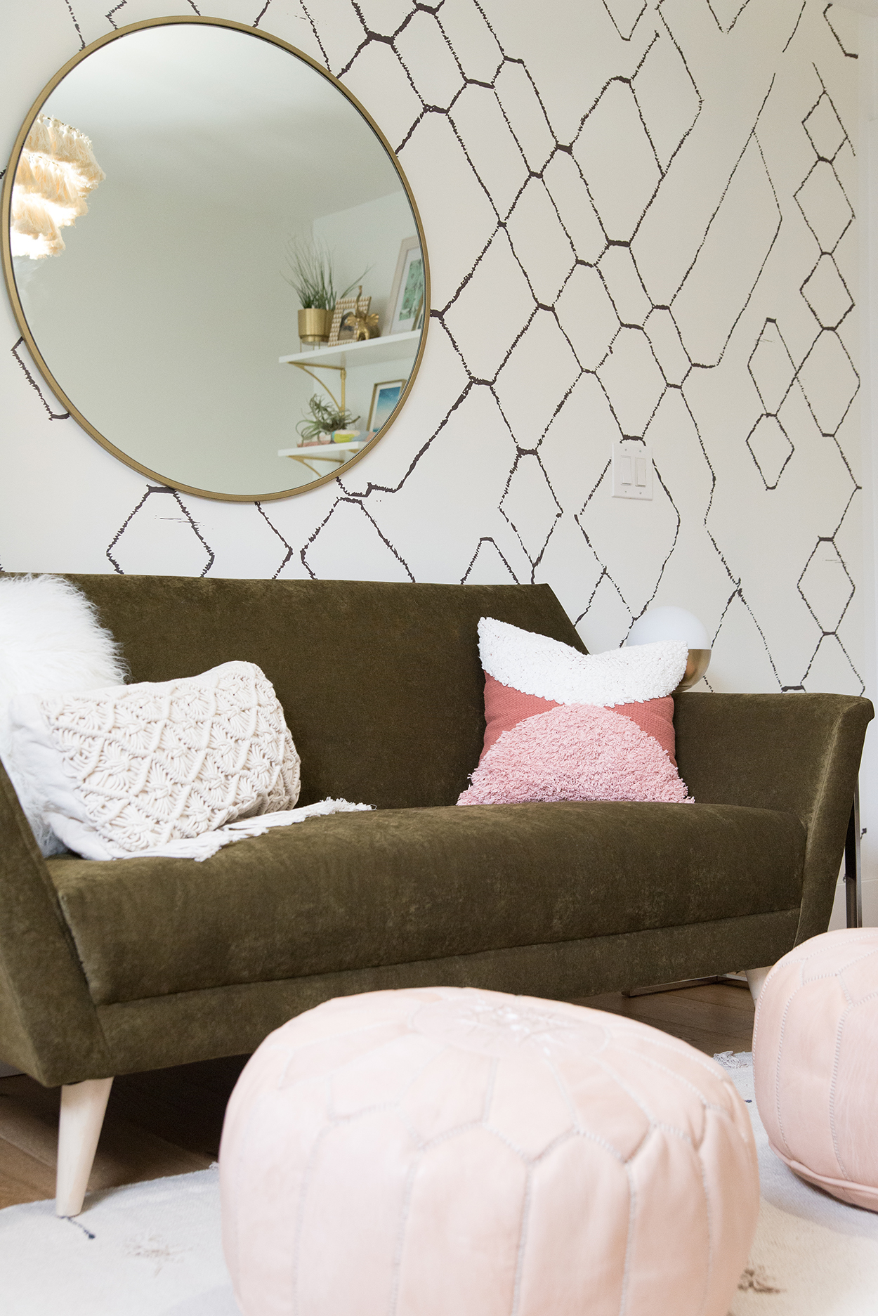 A geometric wallpapered wall with round mirror and a green couch