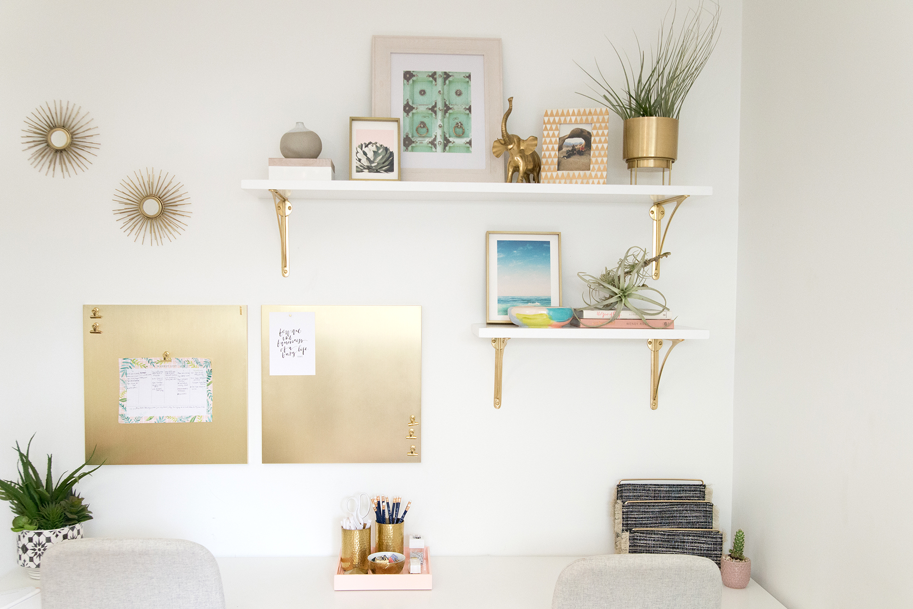 office wall with white and gold shelves and decor